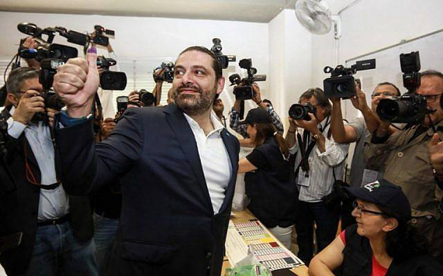 El primer ministro libanés Saad Hariri (CL) hace un gesto de aprobación con su pulgar manchado de tinta después de votar en una mesa electoral en la capital, Beirut, el 6 de mayo de 2018, mientras el país votaba en las primeras elecciones parlamentarias en nueve años.(AFP Photo / Anwar Amro)