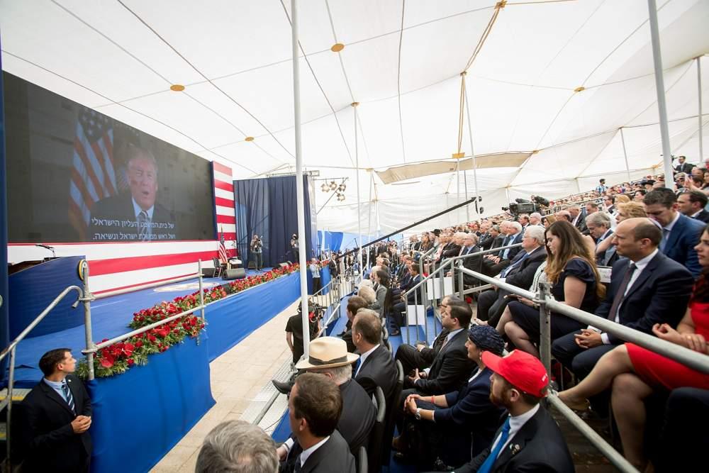 Las personas observan mientras el presidente de EE. UU., Donald Trump, habla en una pantalla de video durante la ceremonia de apertura oficial de la embajada de EE. UU. en Jerusalem el 14 de mayo de 2018. (Yonatan Sindel / Flash 90)