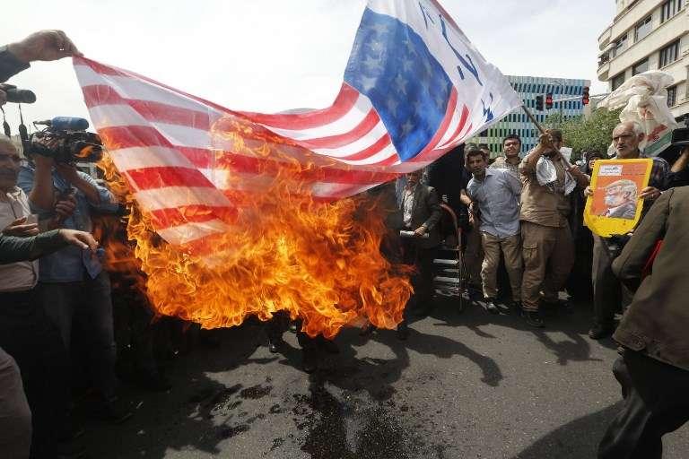 Los iraníes prendieron fuego a una bandera improvisada de los EE. UU. durante una manifestación después de la oración del viernes en la capital, Teherán, el 11 de mayo de 2018. (AFP)