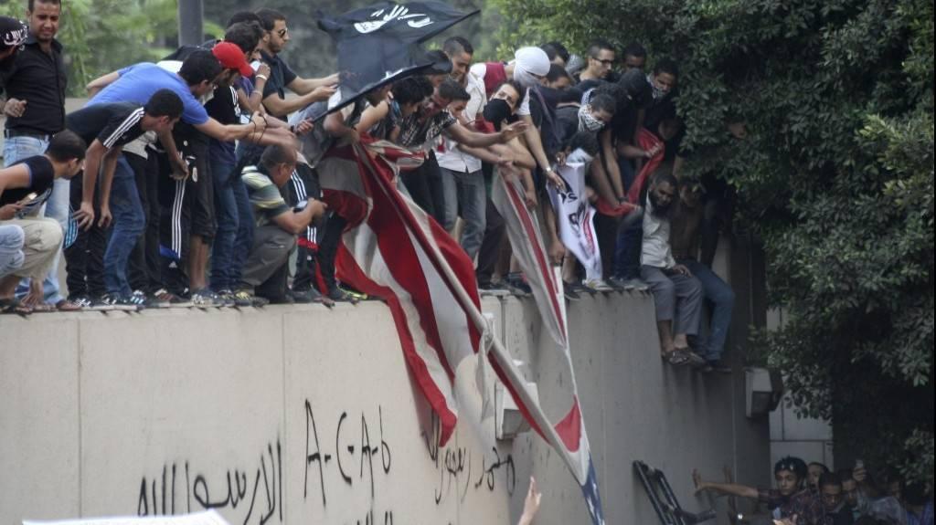 Los manifestantes destruyen una bandera estadounidense en la Embajada de los EE. UU. en El Cairo y la reemplazan con una bandera islámica negra.Treparon por las paredes y protestaban contra una película que consideraban ofensiva para el Islam.(Mohammed Abu Zaid, Foto AP)