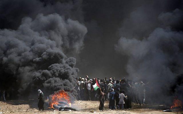 Los palestinos incendian neumáticos cerca de la frontera entre la franja de Gaza e Israel, al este de la ciudad de Gaza, el 14 de mayo de 2018. (AFP Photo / Thomas Coex)