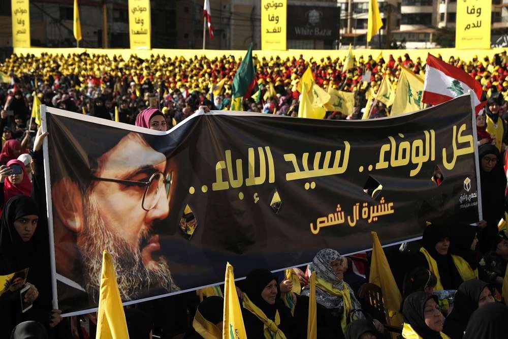 """Los partidarios del líder de Hezbolá Hassan Nasrallah sostienen una pancarta con su retrato y palabras en árabe que dicen: """"Toda la lealtad al hombre de la nobleza"""" durante un discurso de campaña electoral en un suburbio del sur de Beirut, Líbano.(AP / Hussein Malla)"""