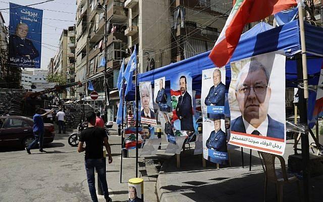 Los retratos de los candidatos del distrito de Beirut, Nouhad Mashnuq, derecha, y del primer ministro Saad Hariri, en el centro, están representados en un barrio residencial de la capital libanesa el 4 de mayo de 2018. (AFP / JOSEPH EID)