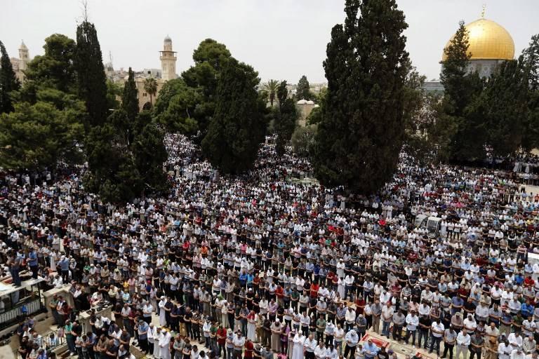 Musulmanes rezan cerca de la Cúpula de la Roca y la Mezquita Al-Aqsa, de la ocupación islámica en el Monte del Templo en Jerusalem, durante las oraciones del segundo viernes del mes sagrado del Ramadán el 25 de mayo de 2018. (AFP Photo / Ahmad Gharabli)