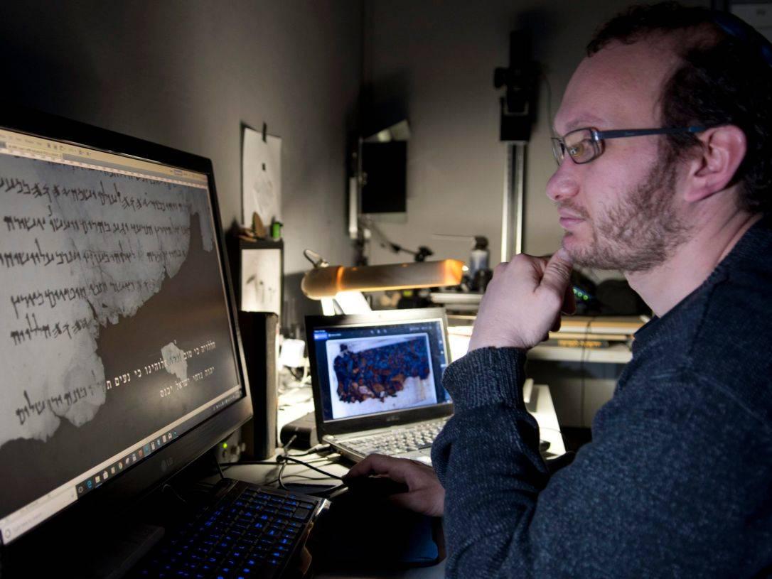 Oren Ableman examina rastros de tinta en las piezas de Rollos del Mar Muerto. Crédito:Shai Halevi, Biblioteca Digital de los Rollos del Mar Muerto de Leon Levy