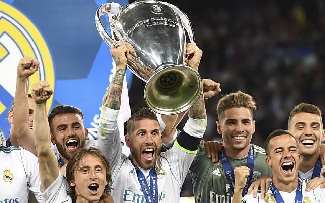 El defensa español del Real Madrid Sergio Ramos levanta el trofeo mientras los jugadores del Real Madrid celebran ganar el partido final de la UEFA Champions League entre el Liverpool y el Real Madrid en el Estadio Olímpico de Kiev, Ucrania el 26 de mayo de 2018. El Real Madrid derrotó al Liverpool por 3-1.(AFP PHOTO / Paul ELLIS)