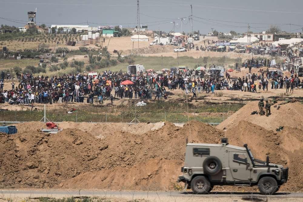 Soldados de las FDI en el lado israelí de la frontera con la Franja de Gaza mientras miles de palestinos se manifiestan cerca de la cerca fronteriza, el 6 de abril de 2018. (Hadas Parush / Flash 90)