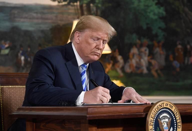 El presidente estadounidense Donald Trump firma un documento que restablece las sanciones contra Irán después de anunciar la retirada de Estados Unidos del acuerdo nuclear de Irán en la sala de recepción diplomática en la Casa Blanca en Washington, DC, el 8 de mayo de 2018. (AFP / Saul Loeb)
