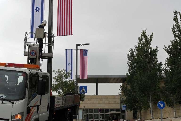 Un trabajador instala decoraciones de banderas israelíes y estadounidenses frente al actual consulado de EE. UU. en Jerusalem, donde los funcionarios estadounidenses instalarán la nueva embajada de EE. UU. el 14 de mayo.(AFP / Thomas Coex)