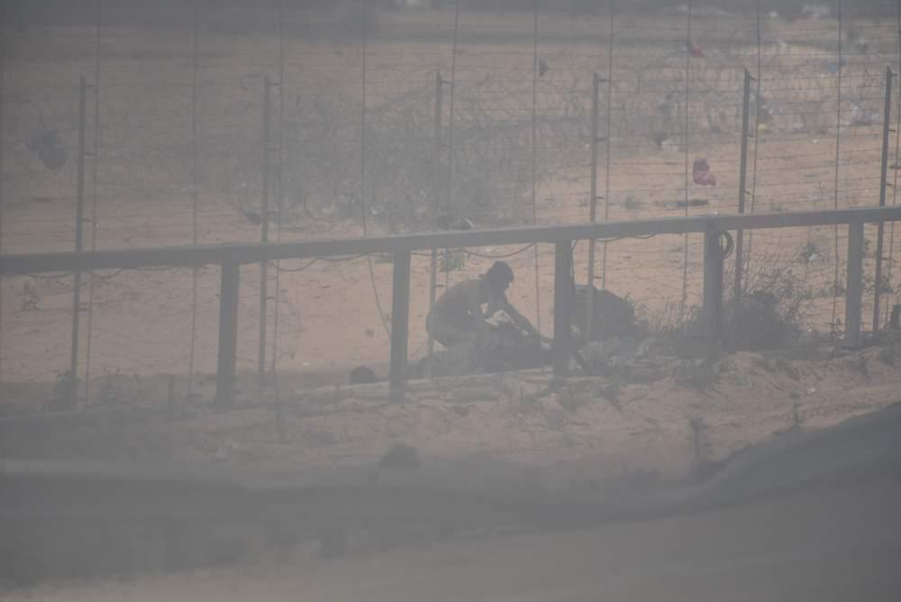 Un grupo de islamistas palestinos intenta colocar un artefacto explosivo a lo largo de la valla de seguridad de Gaza, bajo la protección de un denso humo, durante la violencia masiva a lo largo de la frontera el 14 de mayo de 2018. (Fuerzas de Defensa de Israel)