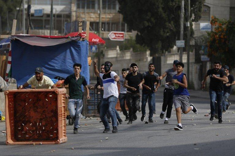 """Islamistas palestinos atacan a soldados israelíes en el llamado """"campo de refugiados"""" al-Amari cerca de Ramallah en Judea y Samaria después de que las tropas asaltaron el campo el 28 de mayo de 2018. (AFP PHOTO / ABBAS MOMANI)"""