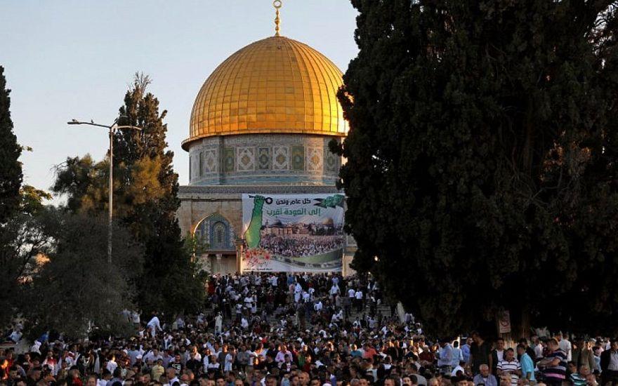 Los musulmanes palestinos realizan la oración de Eid al-Fitr en la mañana cerca de la Cúpula de la Roca en el complejo de la Mezquita Al-Aqsa, el tercer lugar más sagrado del Islam, en la Ciudad Vieja de Jerusalén el 15 de junio de 2018. (AFP / Ahmad Gharabli)