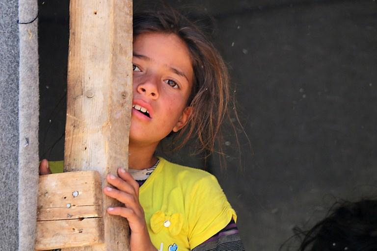 Una niña siria desplazada de Daraa se encuentra en un campamento improvisado en Quneitra, al sudoeste de Siria, cerca de la frontera con Israel, el 22 de junio de 2018. (AFP PHOTO / Ahmad al-Msalam)