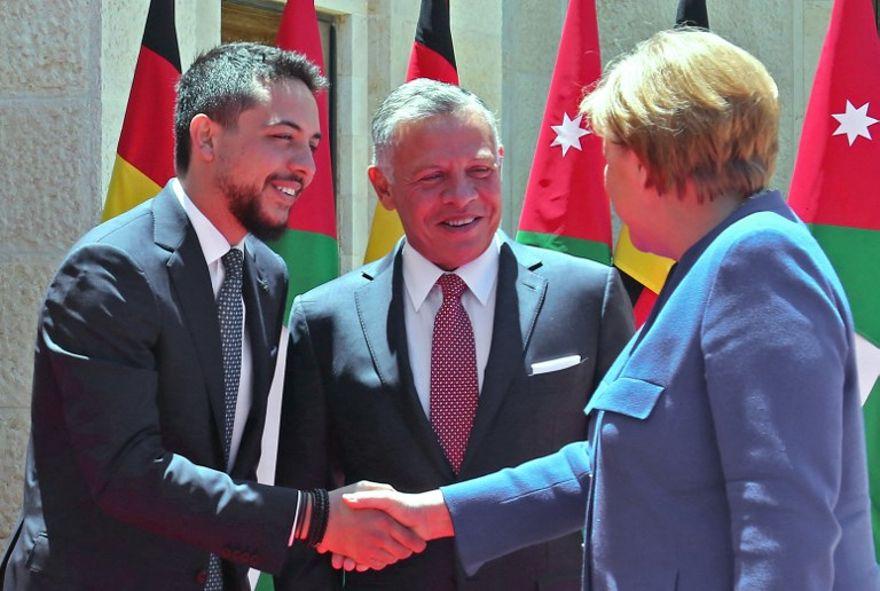 En esta foto tomada el 21 de junio de 2018, el rey jordano Abdullah II (c) y su hijo el príncipe heredero Hussein bin Abdullah (l) dan la bienvenida a la canciller alemana Angela Merkel en el Palacio Real jordano en Amman el 21 de junio de 2018. (AFP PHOTO / Khalil MAZRAAWI)