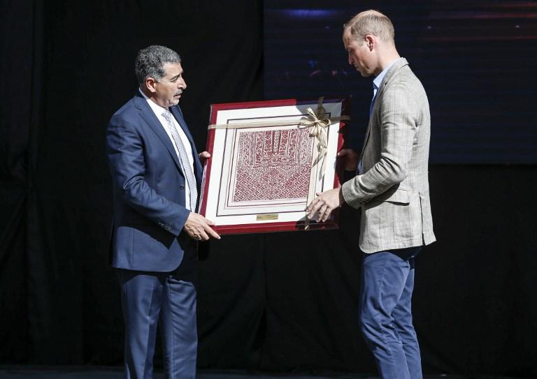 El Príncipe William de Gran Bretaña recibe un regalo de Musa Hadid, el alcalde de Ramallah, en una recepción durante su visita al municipio de la ciudad de Cisjordania el 27 de junio de 2018. (AFP PHOTO / POOL / ABBAS MOMANI)
