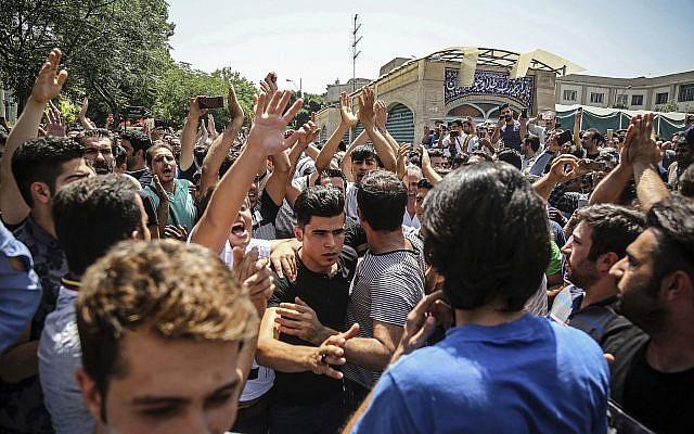 Un grupo de manifestantes grita consignas en la entrada principal del antiguo Gran Bazar en Teherán, Irán, el 25 de junio de 2018. (Agencia de noticias del trabajo iraní vía AP)