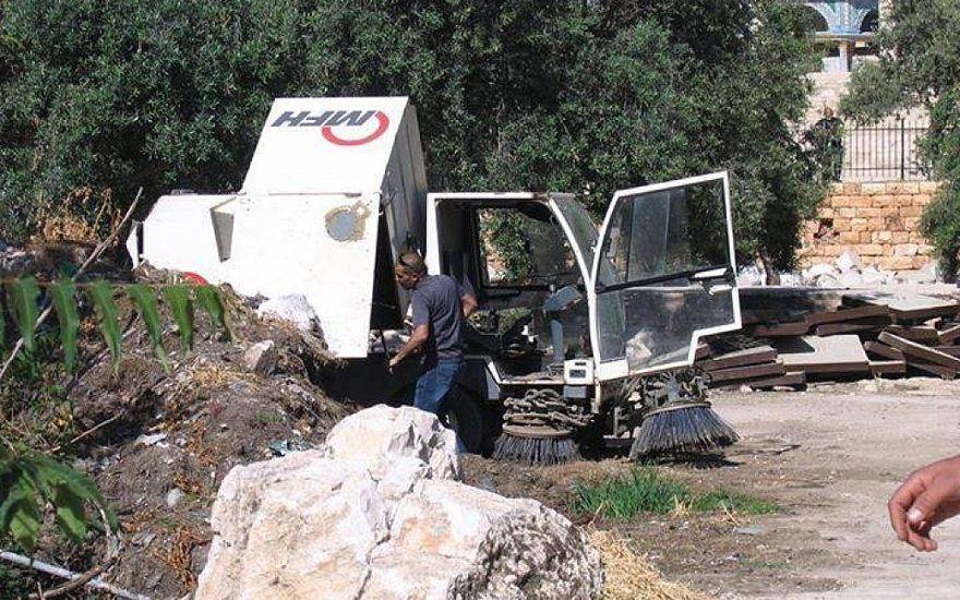 En abril de 2014, un limpiador de calles de Waqf vierte tierra en la pila de tierra de las excavaciones en el Monte del Templo / Compuesto Al-Aqsa. (Cortesía del Comité Público para la Prevención de la Destrucción de Antigüedades en el Monte del Templo)