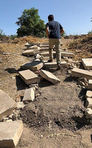 El arqueólogo Zachi Dvira sube por una escalera improvisada tallada en un suelo gris ceniciento en el Monte del Templo, el 18 de junio de 2018. (Amanda Borschel-Dan / Times of Israel)