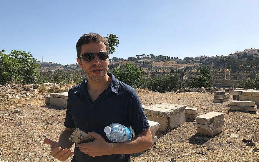 El arqueólogo Zachi Dvira se para frente a lo que dijo que eran mesas improvisadas y bancos creados a partir de losas de piedra encontradas en un montículo de tierra antigua en el Monte del Templo, el 18 de junio de 2018. (Amanda Borschel-Dan / Times of Israel)