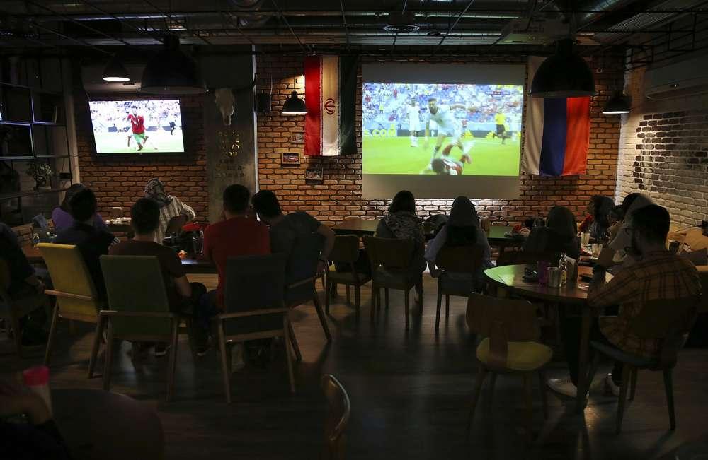 Los iraníes miran a la selección nacional de fútbol jugar contra Marruecos en la Copa Mundial 2018, en un café en el centro de Teherán, Irán, el 15 de junio de 2018. (AP Photo / Vahid Salemi)