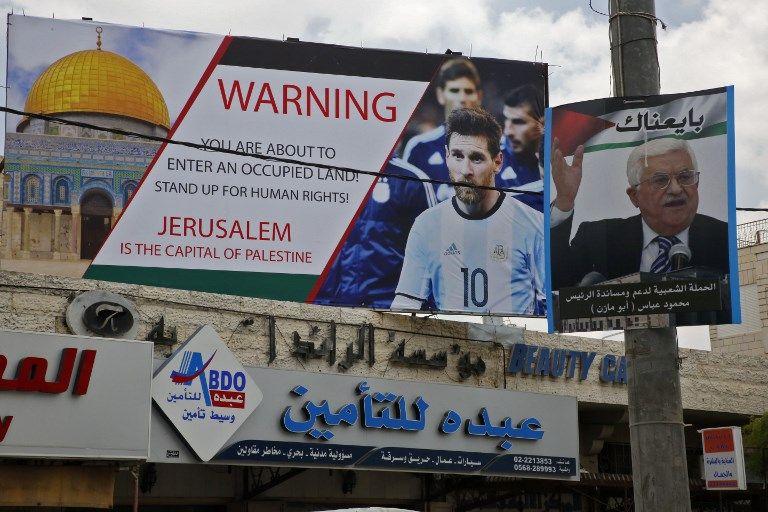Este 5 de junio de 2018, la imagen muestra un cartel erigido en la ciudad de Hebrón llamando a boicotear a la estrella de fútbol Lionel Messi (l) junto a un retrato del presidente de la Autoridad Palestina Mahmoud Abbas.(AFP PHOTO / HAZEM BADER)