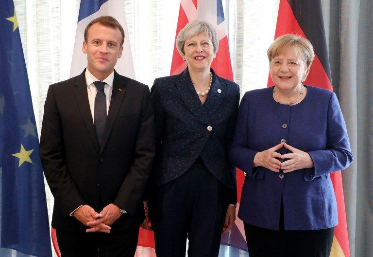 El presidente francés Emmanuel Macron, izquierda, la primera ministra británica Theresa May, y la canciller alemana Angela Merkel sonríen mientras posan para las fotos al comienzo de una cumbre UE-Occidente de los Balcanes en Sofía, el 17 de mayo de 2018. (Ludovic MARIN / AFP)