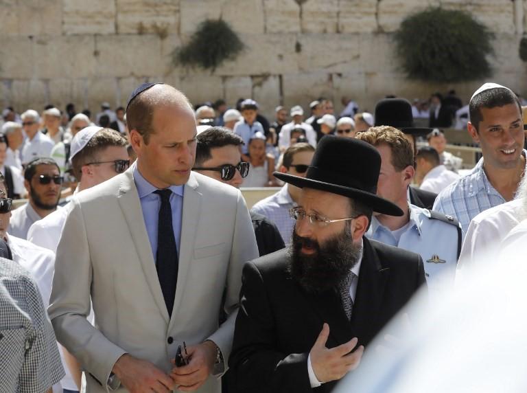 El príncipe Guillermo (CL) de Gran Bretaña camina junto al jefe del Muro de los Lamentos, Rabino Shmuel Rabinovitch (R) durante una visita al Muro Occidental, el lugar más sagrado donde los judíos pueden orar, en la Ciudad Vieja de Jerusalén el 28 de junio de 2018 (AFP PHOTO / Menahem KAHANA)