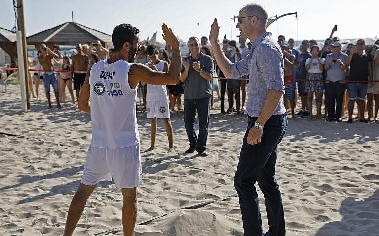 El Príncipe William (R) festeja con un jugador de voleibol playa durante una visita con el alcalde de Tel Aviv en la ciudad costera el 26 de junio de 2018 (AFP PHOTO / POOL / MENAHEM KAHANA)