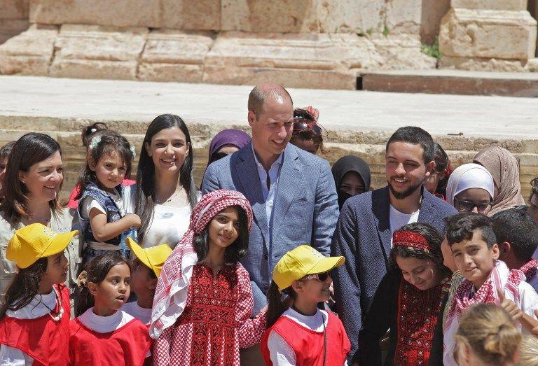 El príncipe William (C) de Gran Bretaña y el príncipe heredero jordano Hussein bin Abdullah (R) conversan con escolares sirios y jordanos durante su visita al sitio arqueológico de Jerash, el 25 de junio de 2018 (AFP PHOTO / AHMAD ABDO)