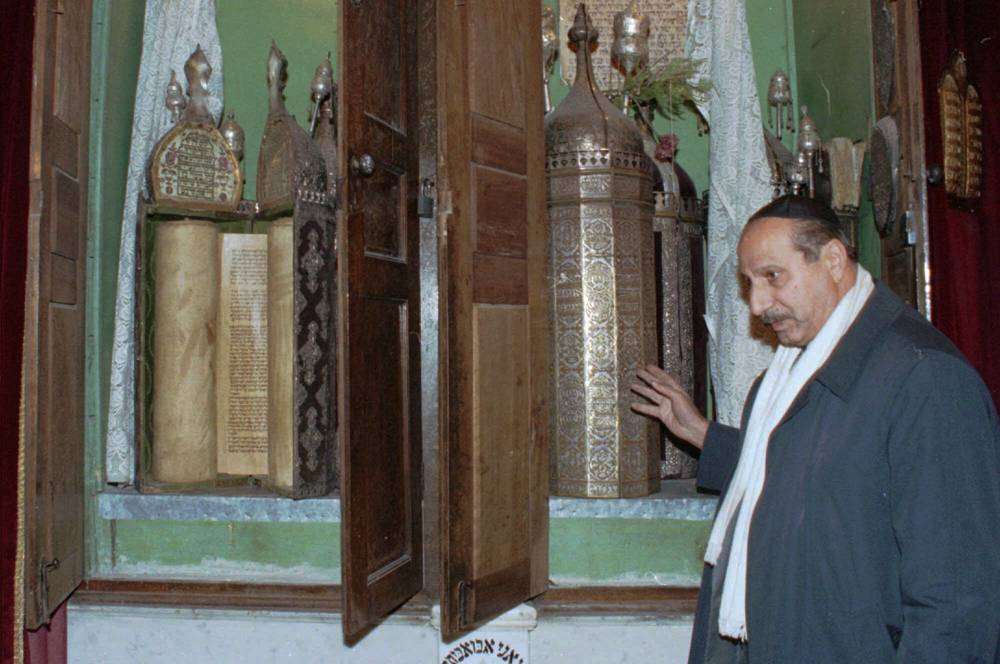 En esta foto de archivo del 21 de enero de 2000, Youssef Jajati, un líder de la comunidad judía en Siria, apunta a los rollos de la Torá conservados en un contenedor de plata en la sinagoga Jobar en Damasco.(AP Photo / Bassem Tellawi, Archivo)