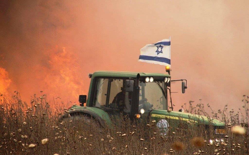 Una foto sin fecha de un agricultor israelí en el área periférica a Gaza que conduce su tractor al lado de un campo incendiado por una cometa encendida que vuela desde la Franja de Gaza.(Cortesía)