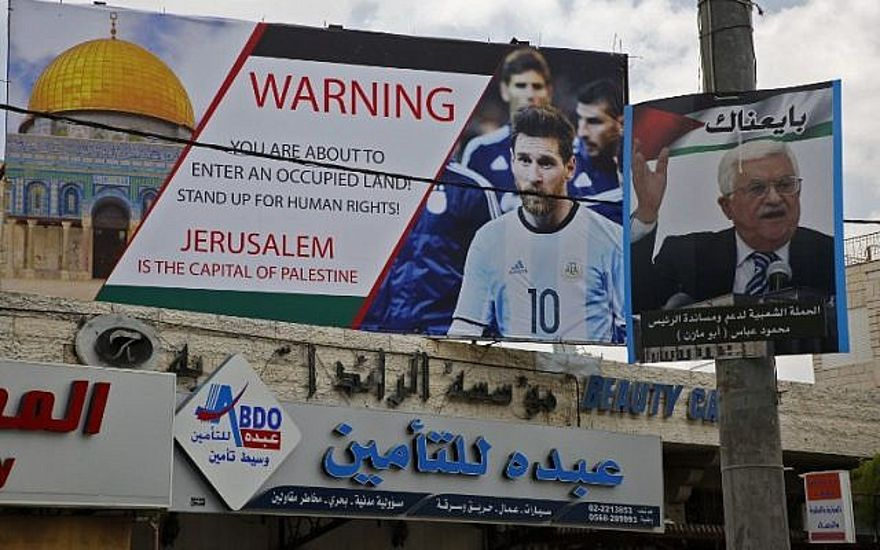 Este 5 de junio de 2018, la imagen muestra un cartel erigido en la ciudad cisjordana de Hebrón llamando a boicotear a la estrella de fútbol Lionel Messi (l) junto a un retrato del presidente de la Autoridad Palestina Mahmoud Abbas