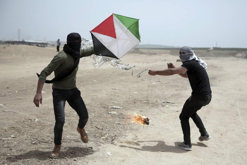 Islamistas palestinos vuelan una cometa con un trapo encendido colgando de la cola durante una protesta en la frontera de la Franja de Gaza con Israel, el 20 de abril de 2018. (AP Photo / Khalil Hamra)