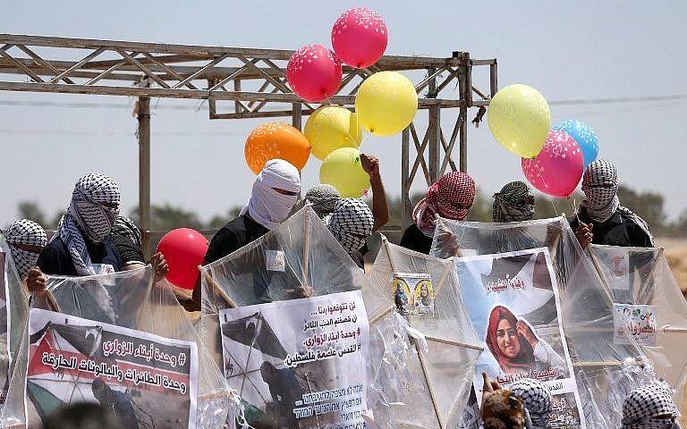 Los palestinos cargan cometas y globos con material inflamable para volar hacia Israel, en la frontera entre Israel y Gaza en al-Bureij, en el centro de la Franja de Gaza, el 14 de junio de 2018. (AFP Photo / Mahmud Hams)
