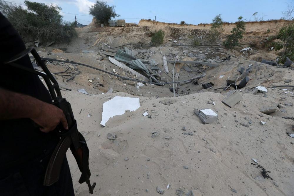 Un militante palestino monta guardia cerca de la base militar destruida de la Jihad Islámica luego de ser blanco de un avión de combate israelí, el sur de la Franja de Gaza el 30 de mayo de 2018. IBRAHEEM ABU MUSTAFA / REUTERS