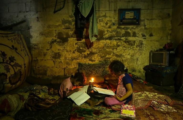 Ilustrativo: niños palestinos hacen sus deberes a la luz de las velas durante un corte de energía en la ciudad de Gaza el 11 de septiembre de 2017. (AFP Photo / Mahmud Hams)