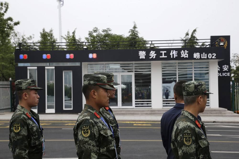 Soldados vigilan cerca de una estación de policía en el centro de medios de la cumbre de la Organización de Cooperación de Shanghai (OCS) en Qingdao, provincia de Shandong, este de China, el sábado 9 de junio de 2018. (AP Photo / Dake Kang)