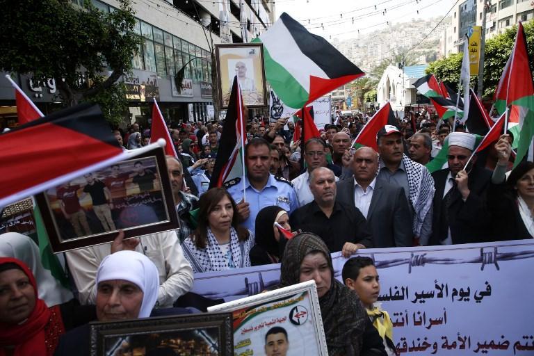 Árabespalestinos sostienen retratos de familiares terroristas encarcelados en prisiones israelíes mientras protestan para exigir su liberación durante una manifestación para conmemorar el Día del Preso en la ciudad de Nablus, el 17 de abril de 2018. (AFP PHOTO / JAAFAR ASHTIYEH)