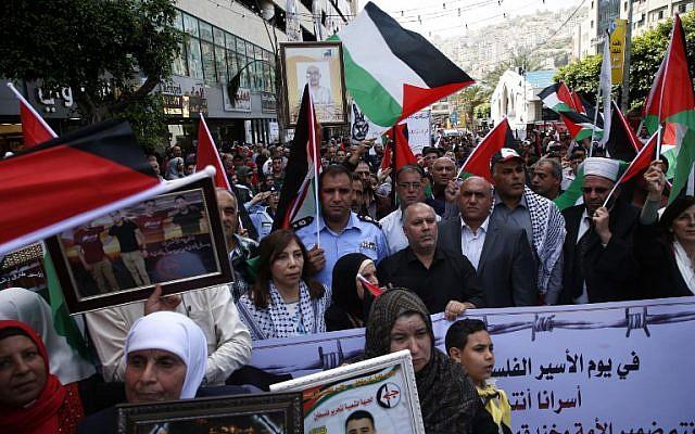 Los palestinos sostienen retratos de familiares encarcelados en prisiones israelíes mientras protestan para exigir su liberación durante una manifestación para conmemorar el Día del Preso en la ciudad de Nablus, al norte de Cisjordania, el 17 de abril de 2018. (AFP PHOTO / JAAFAR ASHTIYEH)