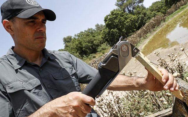 """Yaniv Bar, un ex oficial de inteligencia israelí y cofundador de la start-up """"Aclim8"""", demuestra que está trabajando duro con su herramienta de senderismo """"COMBAR"""" en conjunto, fuera de su oficina en el Kibutz israelí del norte de Israel. Maayan Tzvi el 21 de mayo de 2018 (AFP PHOTO / JACK GUEZ)"""