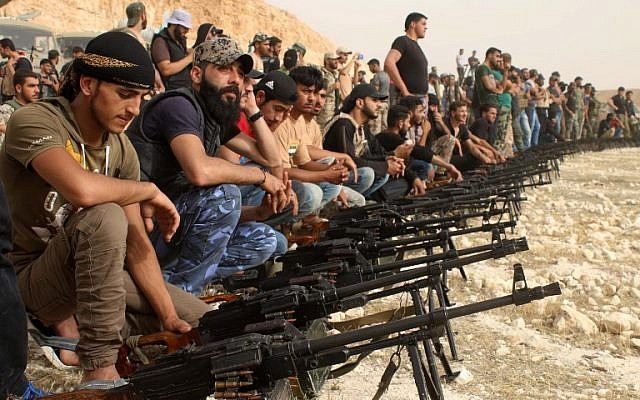 Los rebeldes sirios se sientan detrás de las ametralladoras desplegadas durante un desfile militar cerca de la ciudad sureña de Daraa el 7 de junio de 2018. (Mohamad Abazeed / AFP)