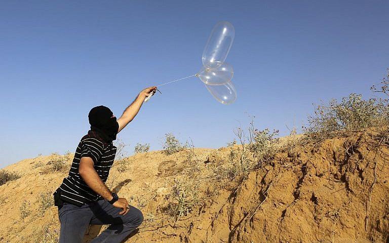 Ilustrativo: un palestino enmascarado lanza un globo cargado con materiales inflamables hacia Israel desde el pueblo de Rafah, al sur de Gaza, el 17 de junio de 2018. (AFP Photo / Said Khatib)