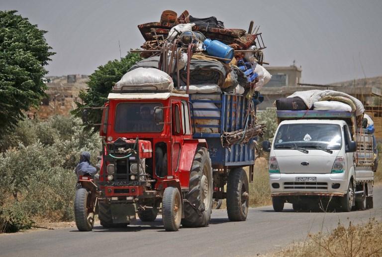 Los sirios desplazados por el bombardeo de las fuerzas gubernamentales en la región sureña de Daraa viajan en tractores y camiones cerca de la ciudad de Shayyah, al sur de la ciudad de Daraa, hacia la zona fronteriza entre las alturas del Golán y Siria, el 28 de junio de 2018. (AFP FOTO / Mohamad ABAZEED)