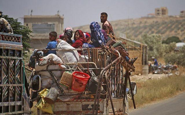 Los sirios desplazados por el bombardeo de las fuerzas gubernamentales en la provincia sureña de Daraa conducen cerca de la ciudad de Shayyah, al sur de la ciudad de Daraa, hacia la zona desmilitarizada que separa las alturas del Golán sirio e israelí el 29 de junio de 2018. (AFP Photo / Mohamad Abazeed )