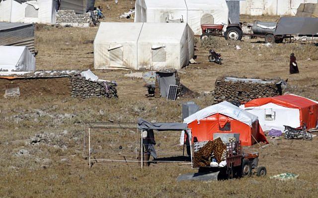 Una fotografía tomada el 30 de junio de 2018, desde los Altos del Golán muestra a los refugiados construyendo una nueva tienda de campaña en un campamento para sirios desplazados cerca de la aldea siria de Burayqah en la provincia sureña de Quneitra. (AFP / JALAA MAREY)