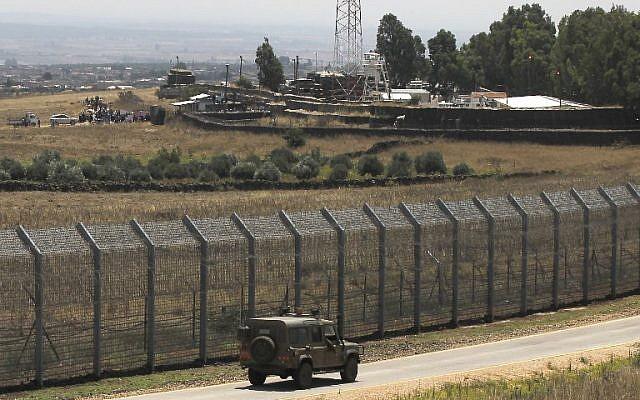 Una imagen tomada el 4 de julio de 2018 desde los Altos del Golán muestra a sirios desplazados de la provincia de Daraa organizando una protesta (parte superior L) pidiendo protección internacional, en la aldea siria de al-Rafid, cerca de la valla fronteriza con Israel. (AFP / Jalaa Marey)