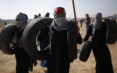 Los palestinos se preparan para quemar neumáticos durante los enfrentamientos semanales de 'Marcha del Retorno' en la frontera de Gaza, al este de la ciudad de Gaza, el 6 de julio de 2018. (AFP Photo / Said Khatib)