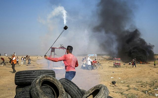 Un palestino utiliza un tirachinas para devolver un bote de gas lacrimógeno a las fuerzas israelíes durante los enfrentamientos a lo largo de la frontera al este de la ciudad de Gaza el 6 de julio de 2018. (AFP Photo / Said Khatib)