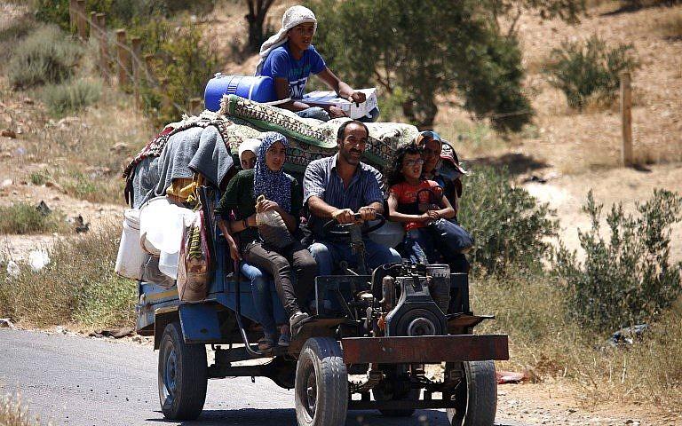Los sirios viajan en un vehículo con sus pertenencias personales cuando regresan a sus hogares en las ciudades y pueblos situados en las afueras al este de Daraa el 7 de julio de 2018. (AFP Photo / Mohamad Abazeed)
