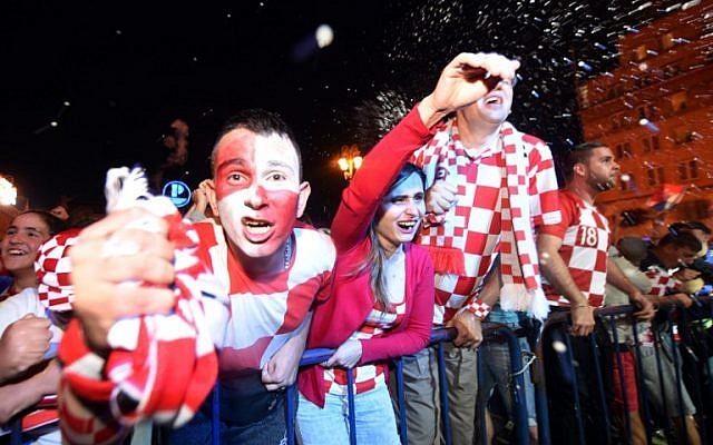 Los seguidores de Croacia celebran después de un gol mientras ven en una pantalla gigante el partido de fútbol semifinal de la Copa Mundial Rusia 2018 entre Croacia e Inglaterra, en la plaza principal de Zagreb el 11 de julio de 2018. (AFP PHOTO / Denis Lovrovic)